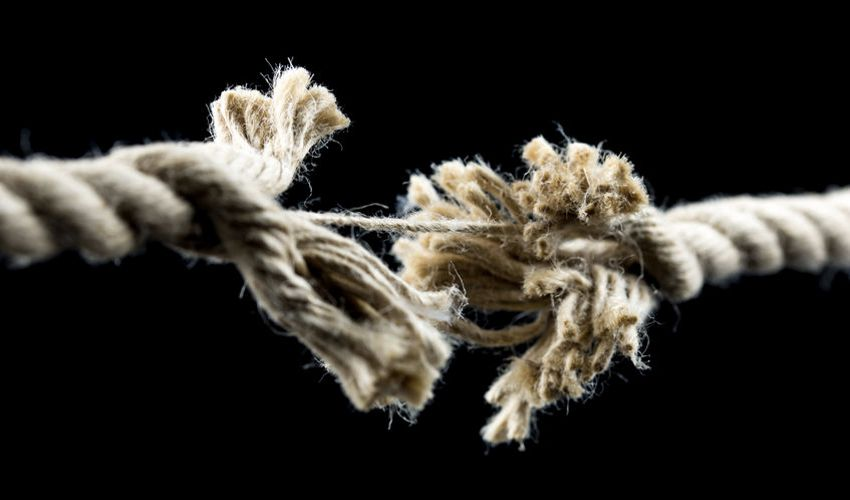 Hanging on by a thread during a crisis - frayed rope.
